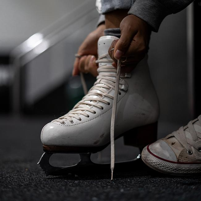Girl putting on ice skates